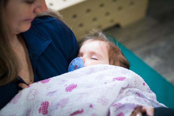 Enfant dormant dans les bras d'une éducatrice